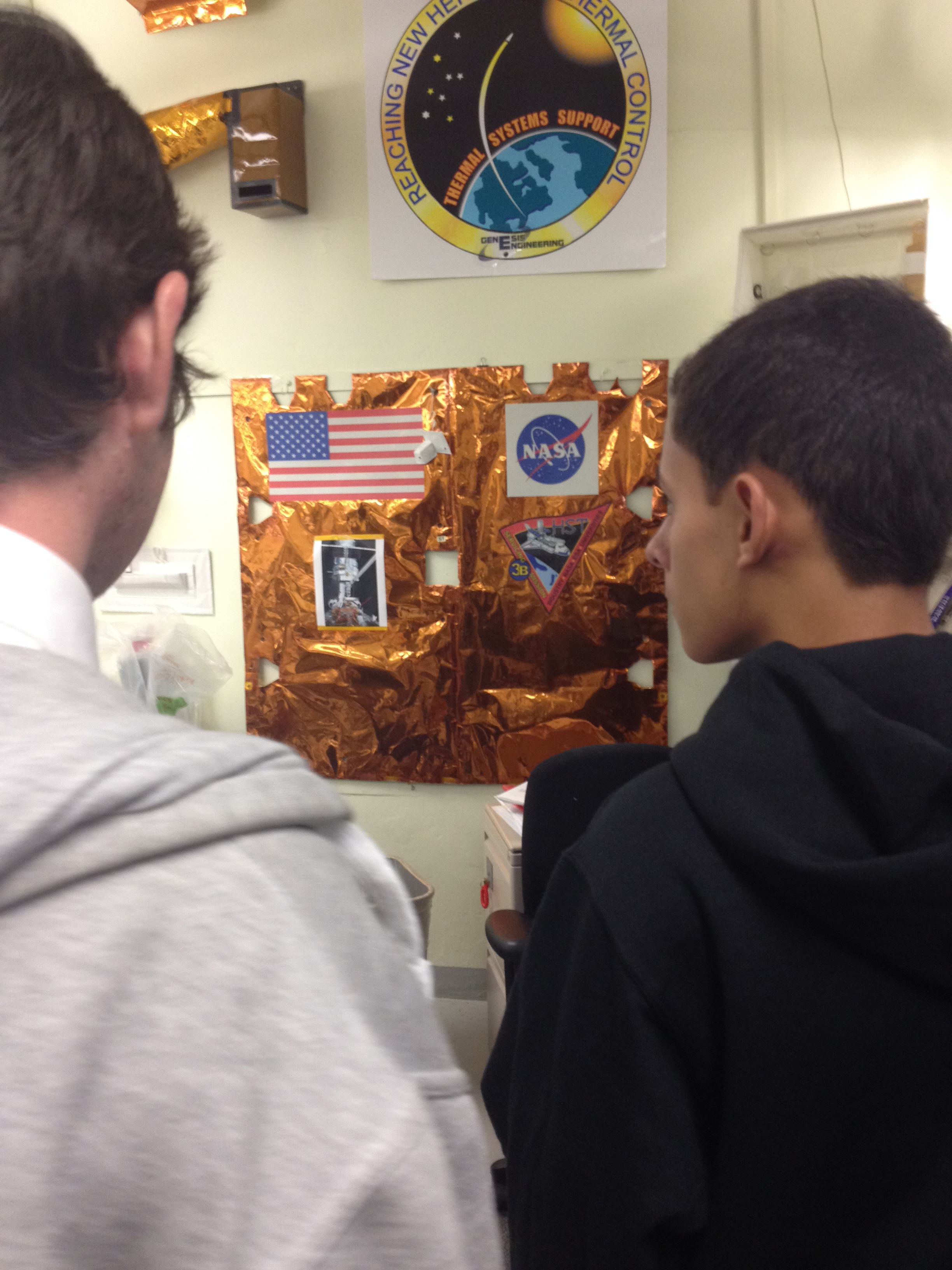 "Steve Smith and José Alvarez examine a piece of the Hubble Telescope's ""space blanket""."
