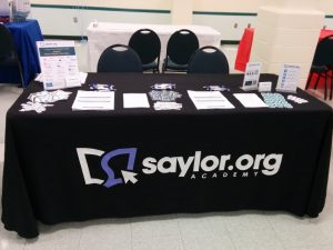 Saylor Academy's table at the Second Annual City of Alexandria Higher Education Fair, showing handouts, stickers, and other materials for the fair attendees.